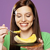 A Smiling Young Woman Taking a Spoonful of Cantaloupe