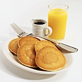 Five Pancakes on a White Plate with a Fork, a Pitcher of Maple Syrup and Orange Juice