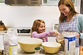 A Woman and a Little Girl Making Oatmeal Cookies in the Kitchen