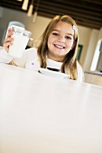 A Little Girl Smiling and Holding a Glass of Milk at a Table