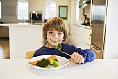 A Little Boy Holding Broccoli on a Fork in Front of a Plate of Mixed Vegetables