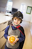 A Little Boy, Dressed as a Knight, Holding an Orange with a Face