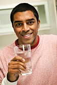 A Man Smiling and Holding a Glass of Water