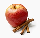 An Apple with Three Cinnamon Sticks
