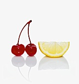 Two Maraschino Cherries with a Lemon Wedge