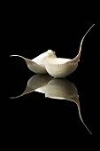 Two Cloves of Garlic on Black with Reflection