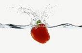 A Red Bell Pepper Splashing into Water