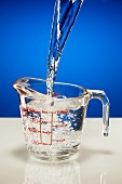 Pouring Water into a Glass Measuring Pitcher