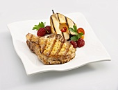 A Grilled Pork Chop with a Grilled Pear Slice and Raspberries