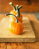 Three Mini Pumpkins on a Wooden Board
