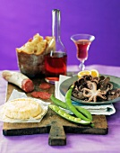 Italian Still Life with Fresh Calamari, Bread, Cheese, Salami, Green Beans and Red Wine on a Wooden Board