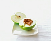 A Halved Granny Smith Apple with Almond Butter on a Square White Plate