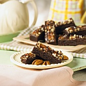 Caramel & pecan brownie bars on a plate and on a tray