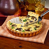 A Slice of Mushroom Quiche Being Lifted from the Pan on a Spatula