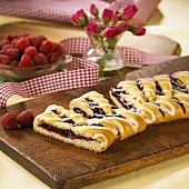 Partially Sliced Raspberry Strudel on a Wooden Board