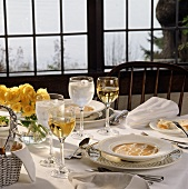 A Tablesetting with Soup and White Wine Next to a Window