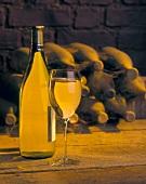 Weißwein in Glas und Flasche vor alten Weinflaschen