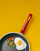 A Skillet with a Fried Egg and Bell Pepper Rings