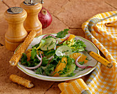 A Green Salad with Orange Segments and a Sesame Breadstick