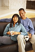Couple having coffee break on sofa