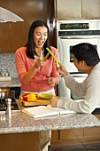 Young couple larking about with celery in kitchen