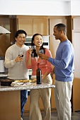 Three people drinking red wine in kitchen