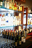 Various Wine Bottles and Wine Glasses at a Bar
