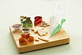Baked Cookies, Cookie Cutters and Decorations on a Wooden Board