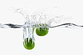 Two Limes Splashing into Water