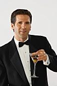 Mann im Smoking hält Martiniglas