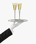 A Gloved Hand Holding a Silver Tray with Two Glasses of Champagne