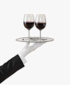 A Gloved Hand Holding a Silver Tray with Two Glasses of Red Wine