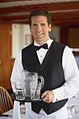 Waiter serving jug of water and glasses in a restaurant