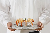 A Waiter Holding a Tray with Shrimp Cocktail
