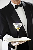 Butler holding glass of Martini on silver tray