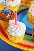 Assorted Cupcakes with Candles on a Colorful Plate