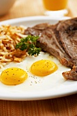 Fried Eggs with Steak and Shredded Homefried Potatoes (Close Up)