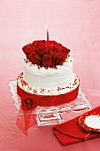 A Valentine's Day Cake with Red Roses and a Lit Candle