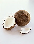 A Whole and an Opened Coconut on White