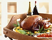 A Whole Roast Turkey on a Wicker Tray with Wine Bottles and Side Dishes
