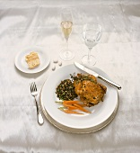 A Place Setting with Cornish Game Hen, Carrots, Wild Rice, Bread, Mints and Wine