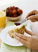 Hände bestreichen Scone mit Erdbeermarmelade