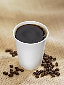 Black Coffee in a Plastic Cup with Coffee Beans