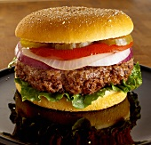 A Thick Angus Burger with Lettuce, Onion, Tomato and Pickles