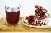 A Glass of Pomegranate Juice with an Opened Pomegranate