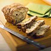 A Partially Sliced Loaf of Cinnamon Apple Bread on a Wooden Board with a Knife