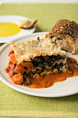 A Piece of Vegetable Lasagna with Carrots, Spinach, Mushrooms and Tomatoes
