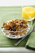 A Bowl of Bran Flake Cereal with Raisins and a Glass of Orange Juice