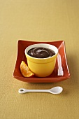 Chocolate Pudding in a Yellow Ramekin with a Slice of Orange