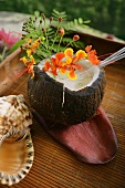 A Coconut Cocktail Served in a Coconut Shell with Flowers